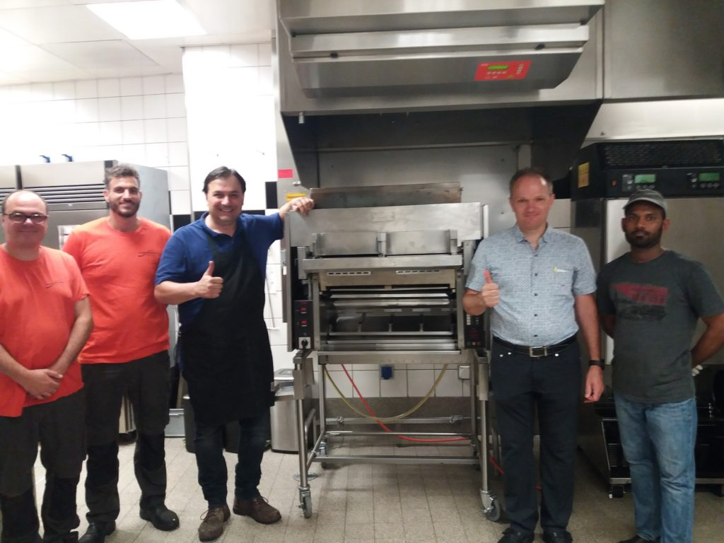 Technicians stand with Nieco Automatic Flame Broiler in a restaurant kitchen